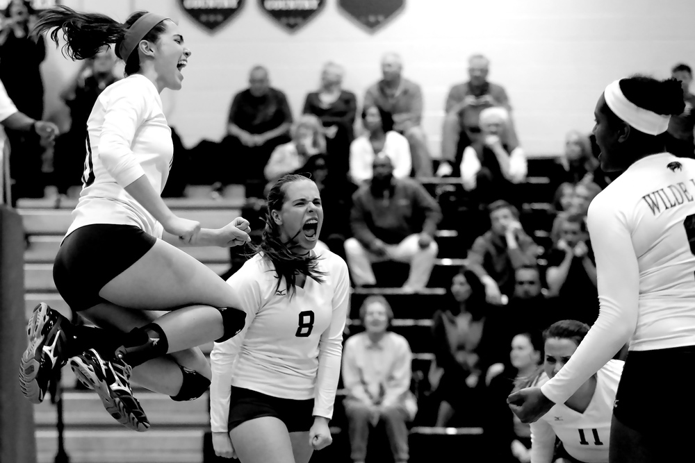 Camille Johnson, left, and Faith Leslie of Wilde Lake celebrate after defeating Reservoir during a regional playoff volleyball game in Columbia, Maryland on November 3, 2014.