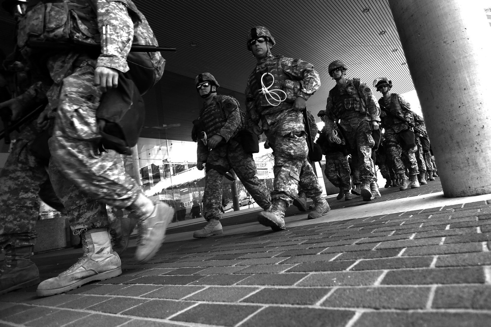 Members of the National Guard walk in front of the Baltimore Convention Center while protestors march after the announcement that all six officers will be charged following the death of Freddie Gray while he was in police custody,  May 1, 2015 in Baltimore, Maryland.
