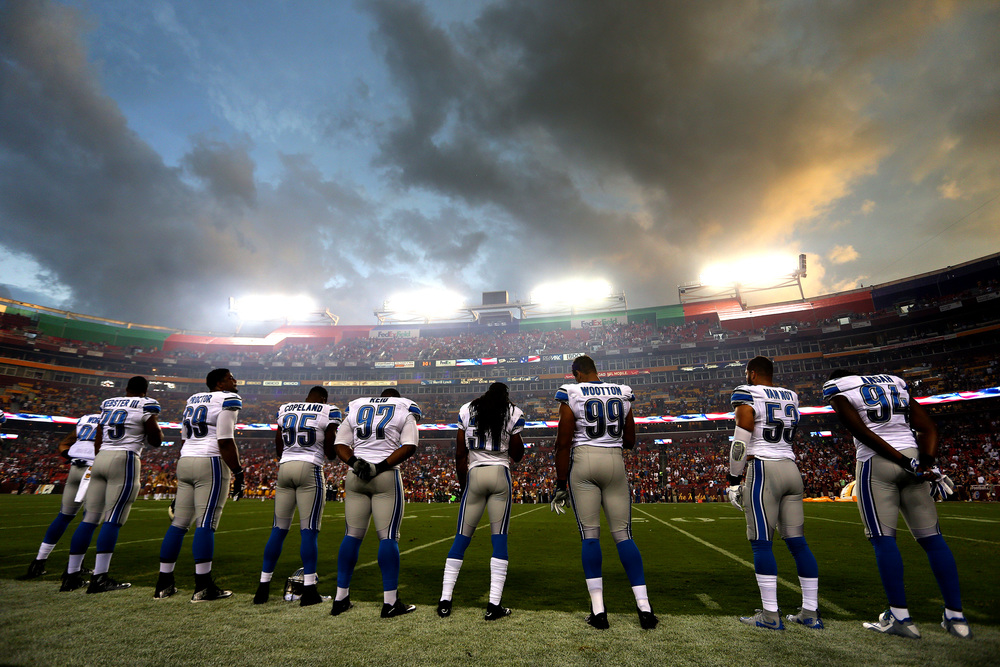 Members of the Detroit Lions stand for the playing of the national anthem before a preseason game against the Washington Redskins at FedEx Field on August 20, 2015 in Landover, Maryland.