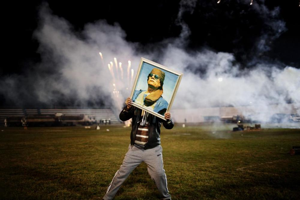 LIBYA. March 9, 2011. A Qaddafi supporter holds a portrait of the Libyan leader as fireworks go up in the background on a soccer field in a suburb of Zawiyah where government minders took a group of foreign journalists to attend a staged celebration.