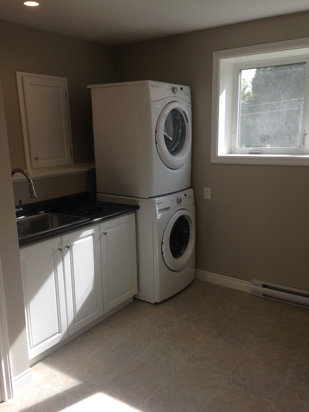 Stacked washer/dryer with sink and cabinets