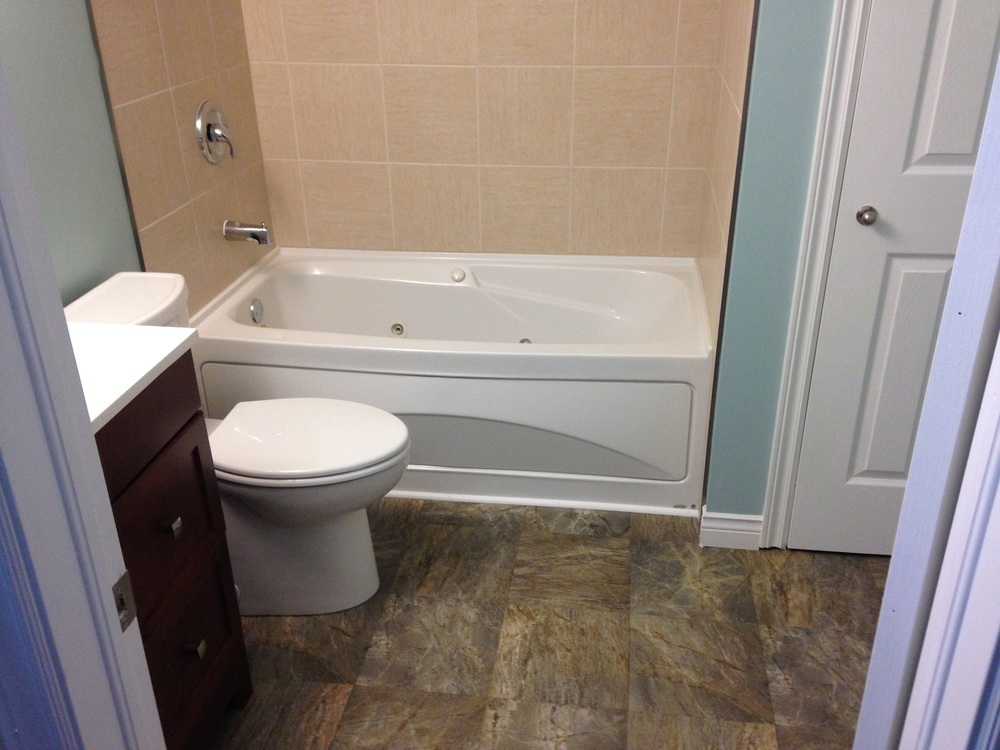 New bathtub with tiled surround, toilet and vanity