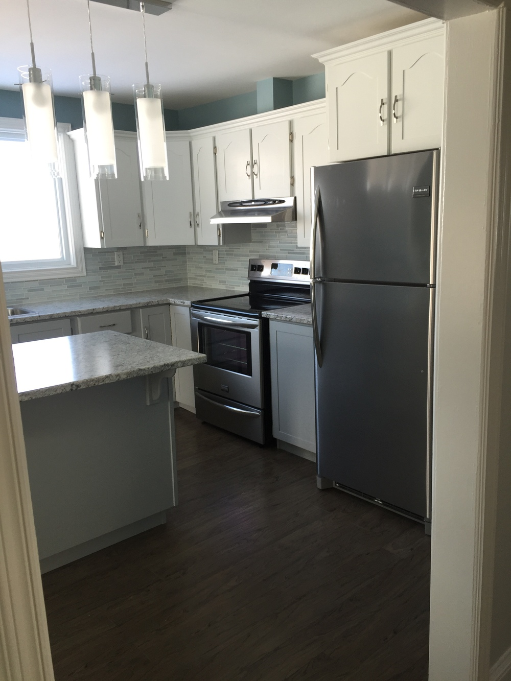 New stainless steel appliances and a glass backsplash provide beautiful finishes.