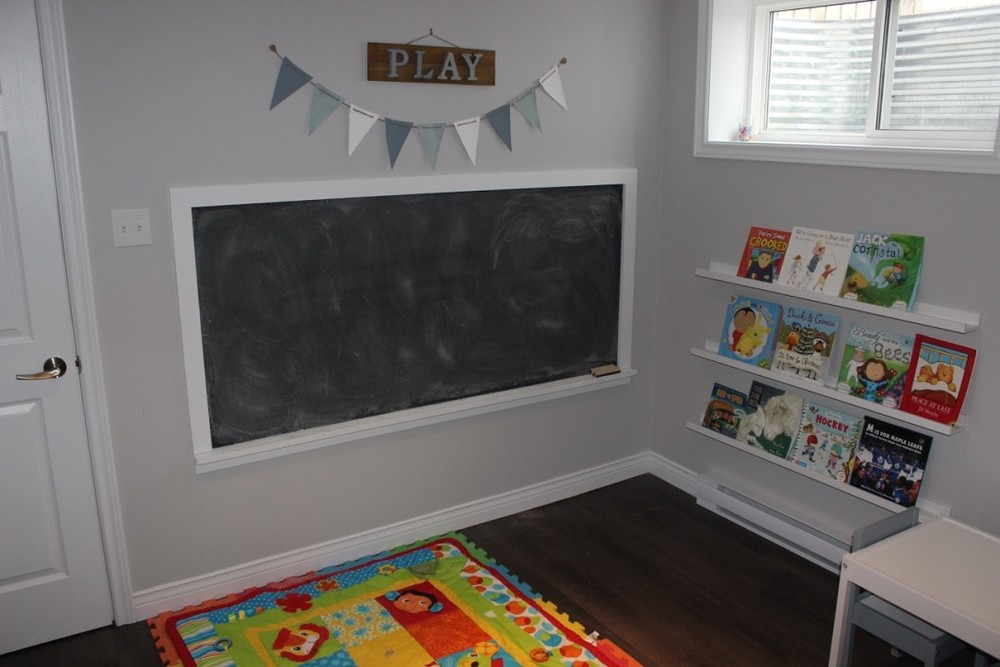 Furnished play area with chaulk board, book shelf and floor mat.