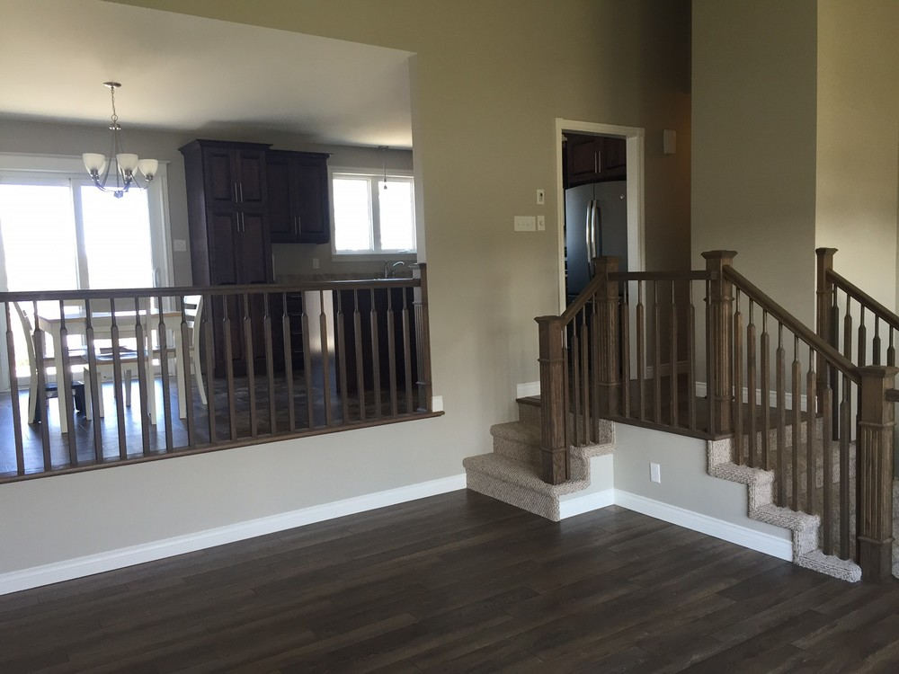 Renovated main floor with new flooring, re-designed stairs, railing and all new finishes.