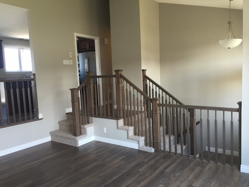 Half-wall rails removed to make way for updated railing and new stairs.  New flooring and finishes throughout.