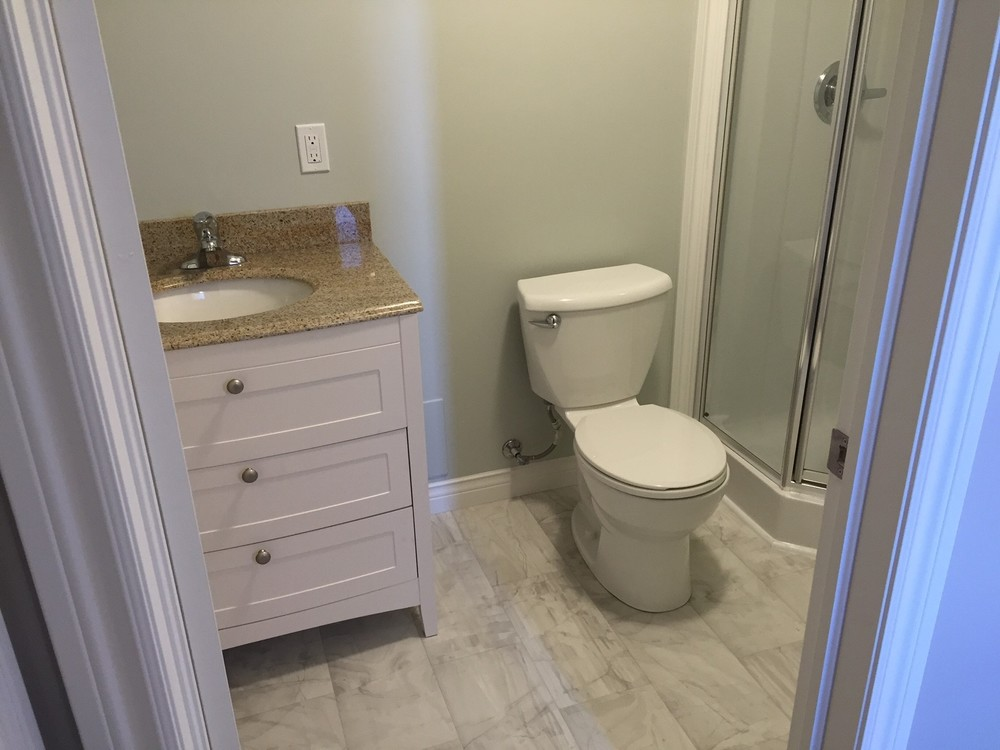 New 3/4 bath with vanity, toilet and corner shower. Fixtures were completely relocated.