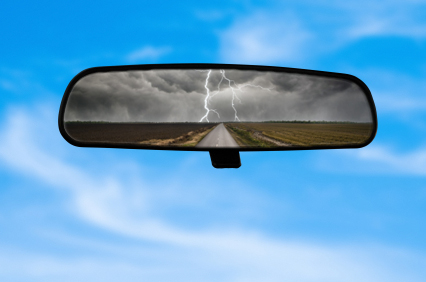 Rear view mirror showing a storm in the background