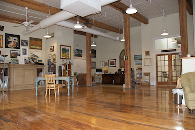 Large room with art hanging on the wall at The Sanctuary of Greensboro, a creative center