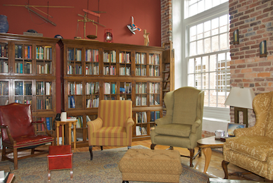 Shelves of books with chairs sitting in a circle at the The Sanctuary of Greensboro, a creative center