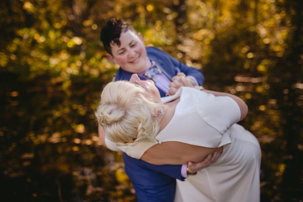 October Jewish lesbian wedding at Foxfire Mountain House in Upstate New York. Bride dipping bride.