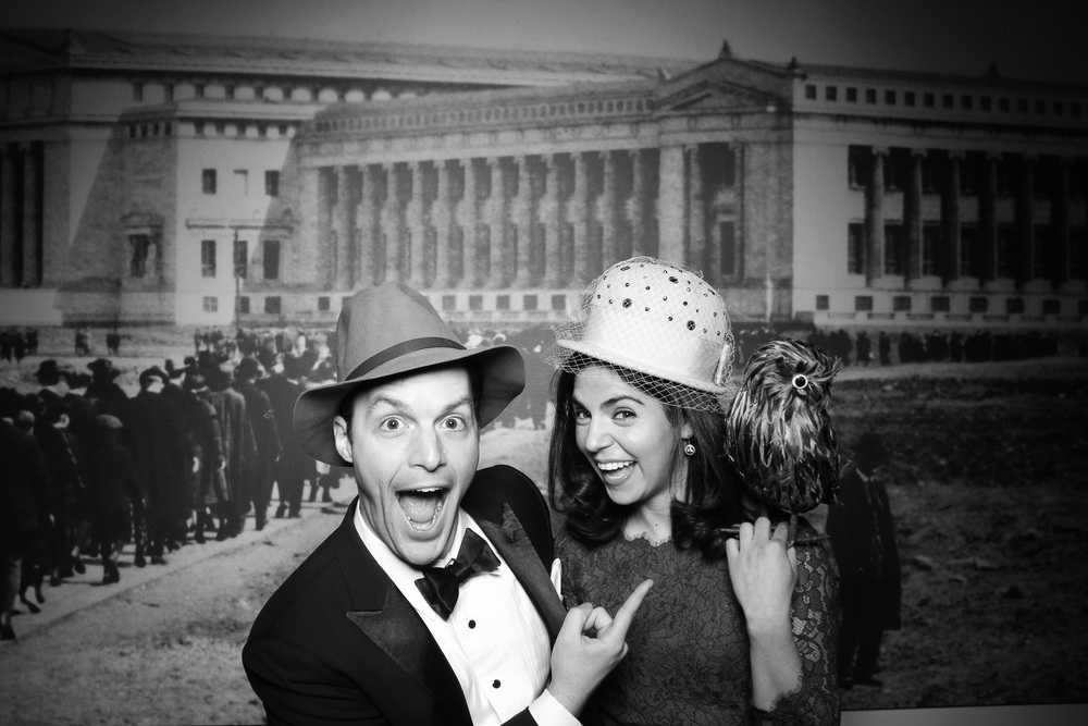 A couple posing for a photo booth picture with vintage props in front of the Field Museum on opening day!