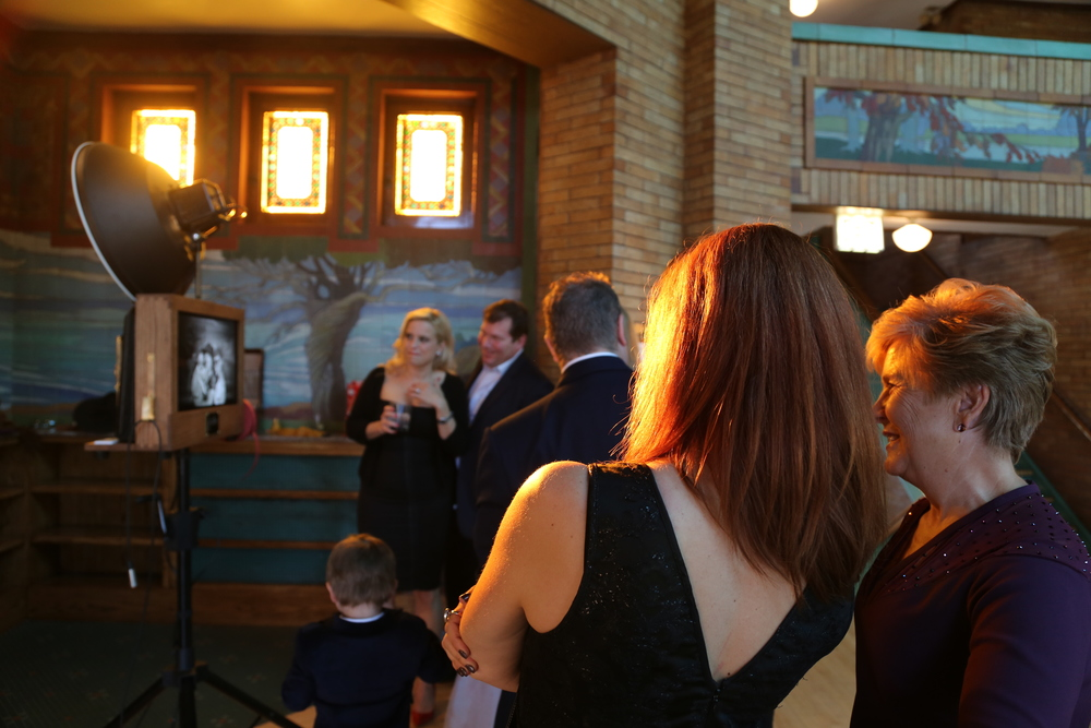 Beautiful sunlight beams through the stained glass at Café Brauer as guests watch the photos on the photo booth slideshow.
