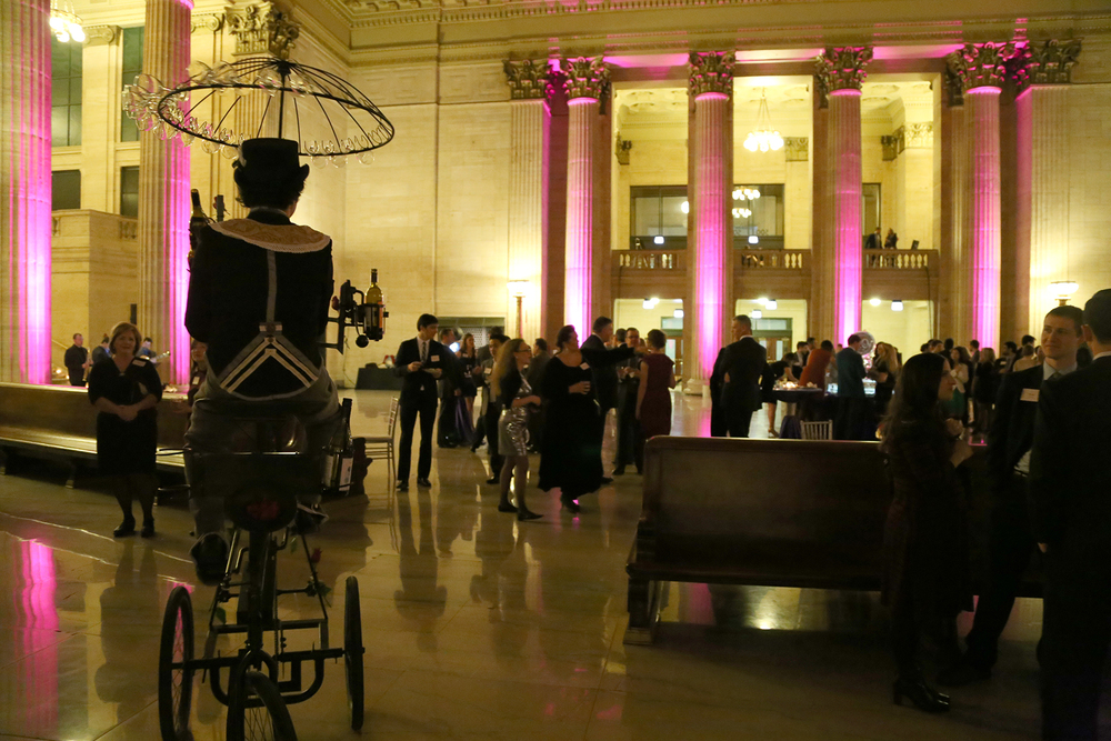 One of Redmoon Theatre's famous wine bikes delivering drinks in the Union Station Great Hall.