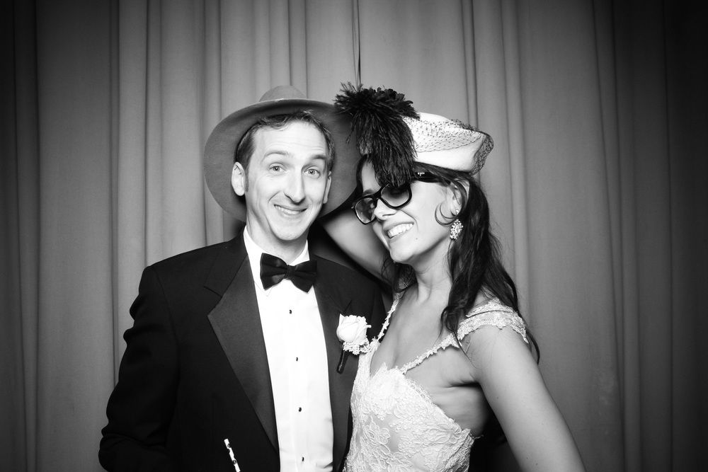 The bride and groom pose for a photo booth picture in Ruggles Hall.