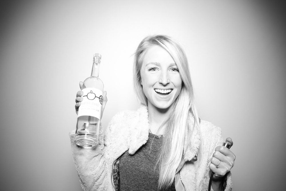 Jenny posing for a photo booth picture with one of the empty Rhine Hall custom bottles. We love the cool and simple design of the labels!