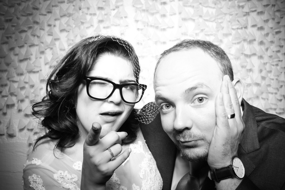 The bride and groom pose for a photo booth picture at their Room 1520 wedding!