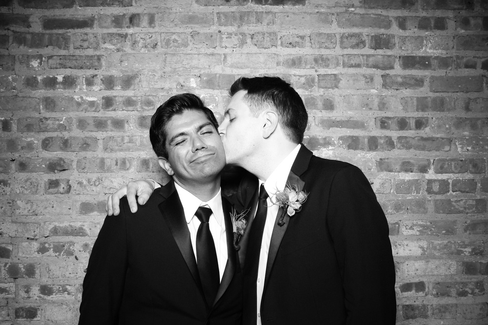 The two grooms take a photo booth picture with the exposed brick at Gallery 1028!