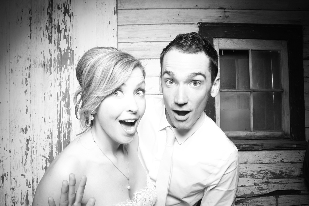 The bride and groom take a photo booth picture in the vintage barn at Heritage Prairie Farms.