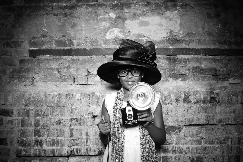 This wedding guest rocked it with a vintage hat and brownie camera! Photo taken by Fotio photo booth at a New Leaf Chicago wedding!