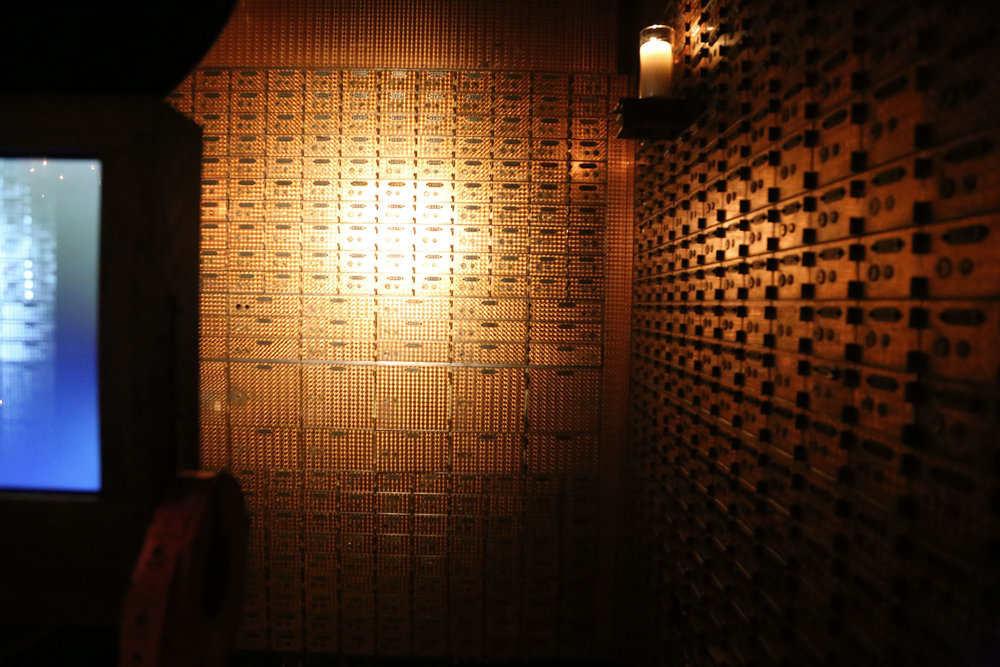 Copper banks boxes adorn the wall.