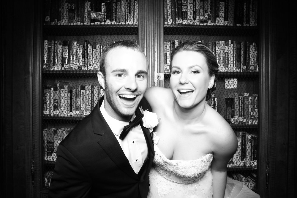 The bride and groom pose for a photo booth picture in the library at Lake Forest Academy!