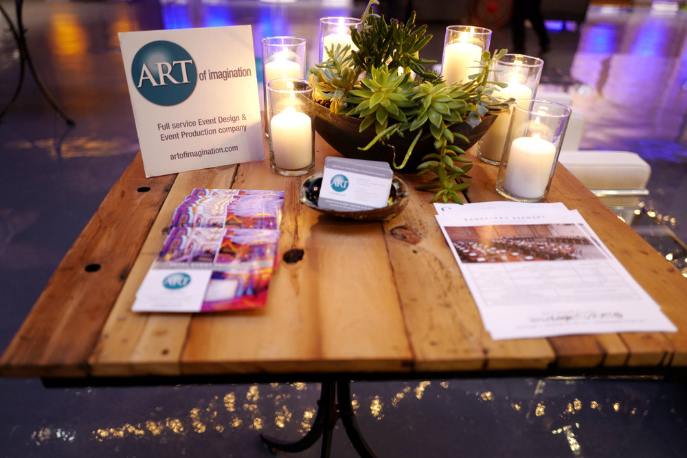 The Art of Imagination info table! LOVED the cafe lights and uplighting on the beer cans etc - they will transform your event!