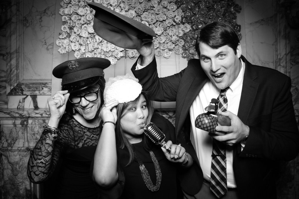 Wedding guests take photo booth pictures in the marble room at Lake Forest Academy