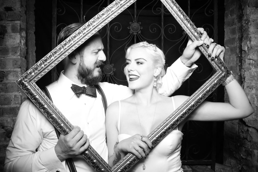 Chelsea and Brian pose for a photo booth picture at their 1920s inspired Salvage One Wedding!
