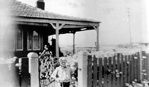 The only known family photo of Morrie Tickner, circa 1932 at the front gate of his parents house in Wickam.   Photo from Newcastle Police archives, Newcastle.