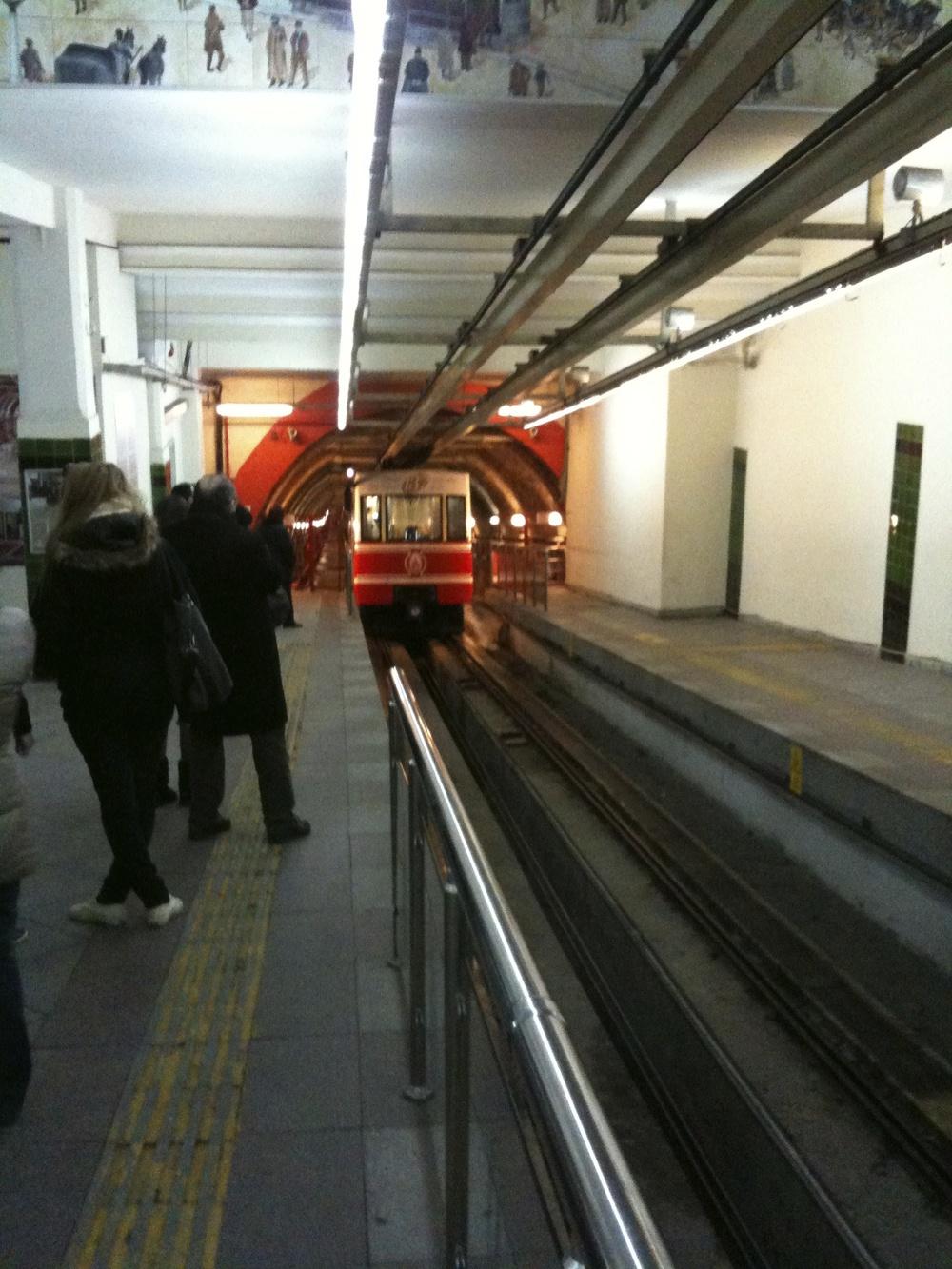 Regarder le petit métro arriver dans le Tünel.