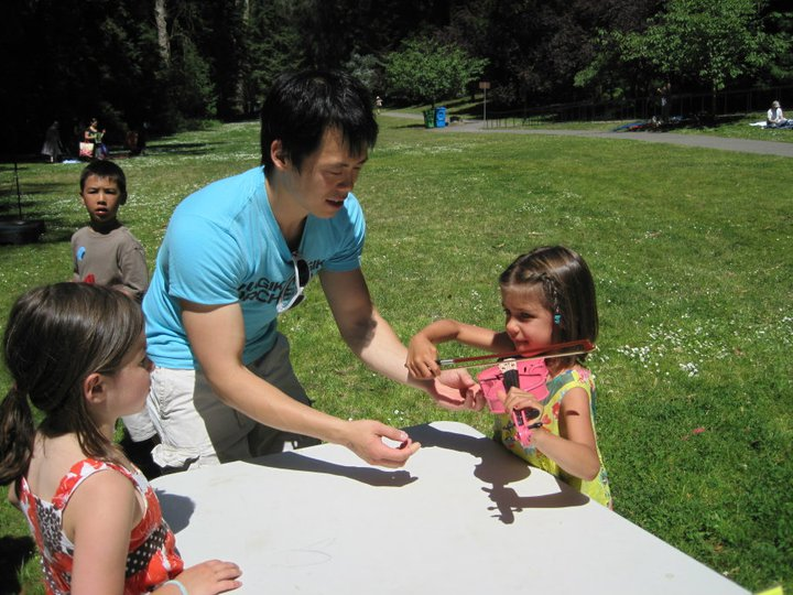 Lucas shows a young visitor how to play violin on a pink instrument just her size.