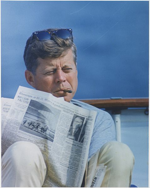 0. Hyannisport_Weekend._President_Kennedy_with_cigar_and_New_York_Times._Hyannisport,_MA,_aboard_the_-Honey_Fitz-._-_NARA_-_194268.jpg