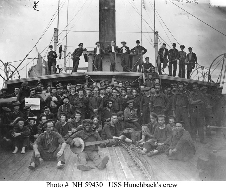 Crew of USS Hunchback during the American Civil War. The crewman to the left of the man holding a newspaper is with a small dog.