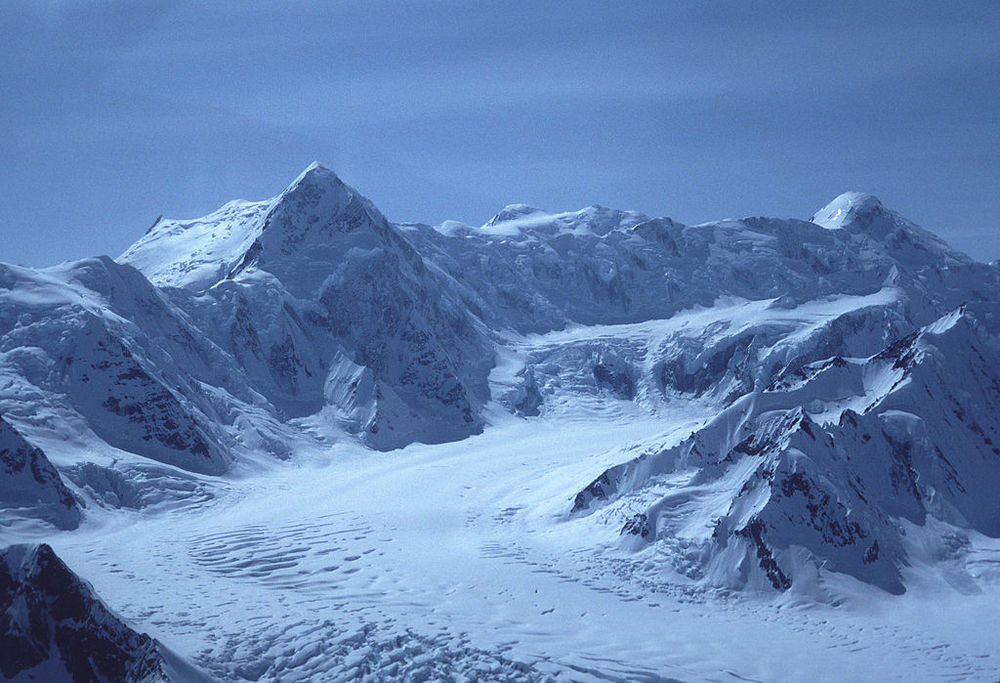 Mount Kennedy as shown from an airplane in 1984. Mount Kennedy is the high peak towards the left. Source: Gary Clark, available  here .