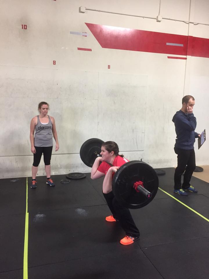 Mary front Squatting while Marianne is waiting her turn in a team competition they did together.