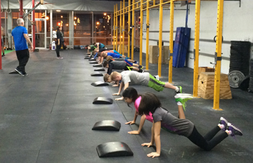 Coach Mike and Katie teaching some push ups to our 6pm class