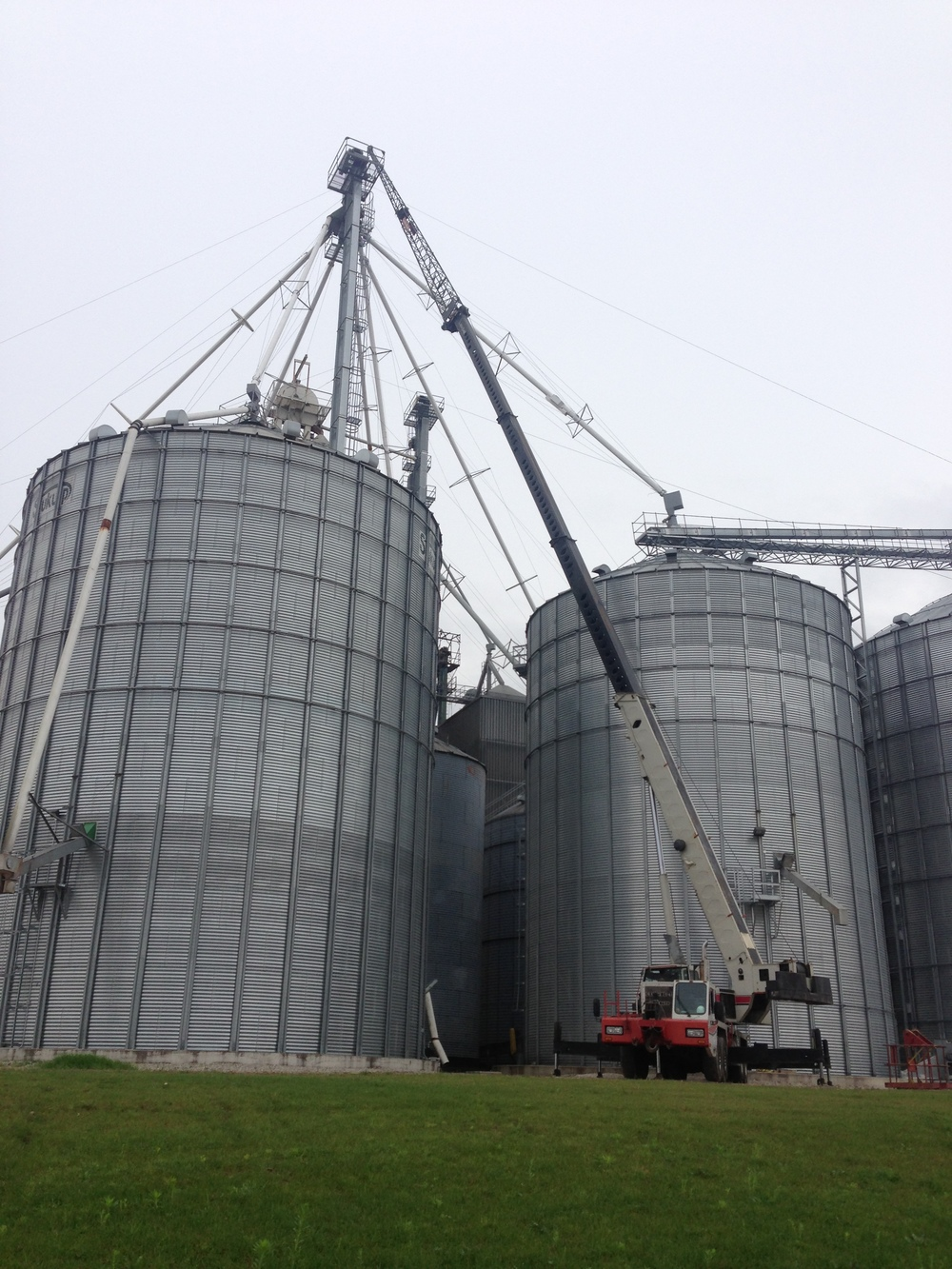 Grain bin spout lifted by mobile crane