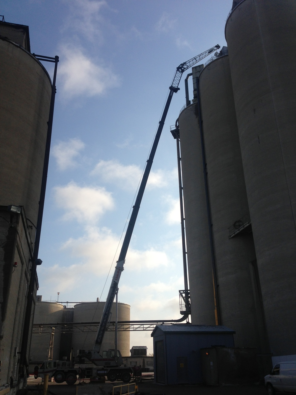 Mobile crane hoisting steel pipe on silo roof on farm