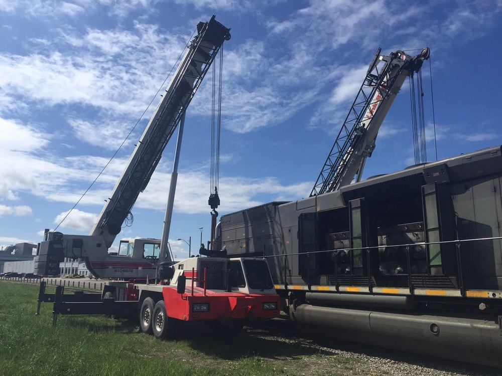 Two mobile cranes lifting a train car to change the motor
