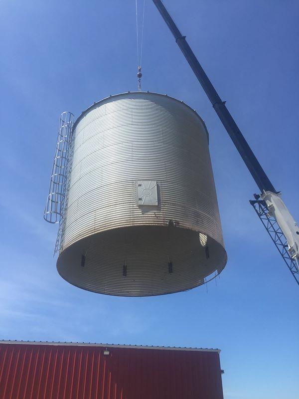 70 ton crane lifting a grain bin on a farm