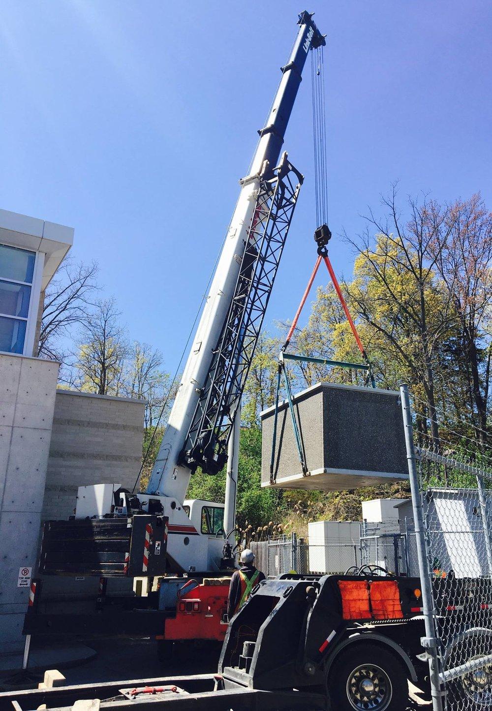 100 ton link belt crane relocating a precast storage shed.