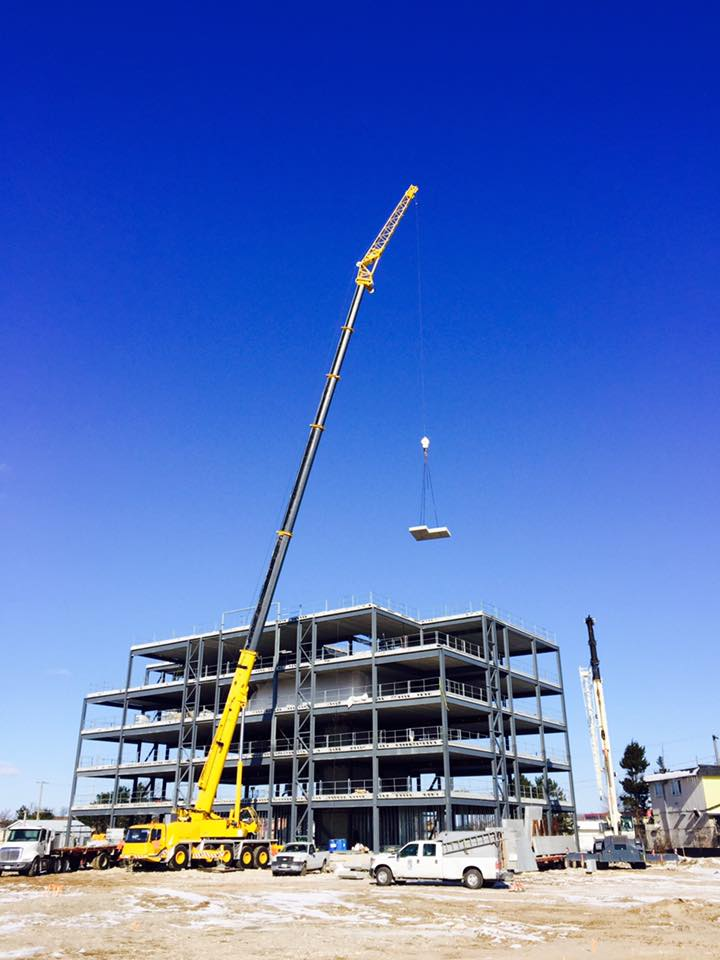 Concrete slab lifted by 165 ton crane on building construction site