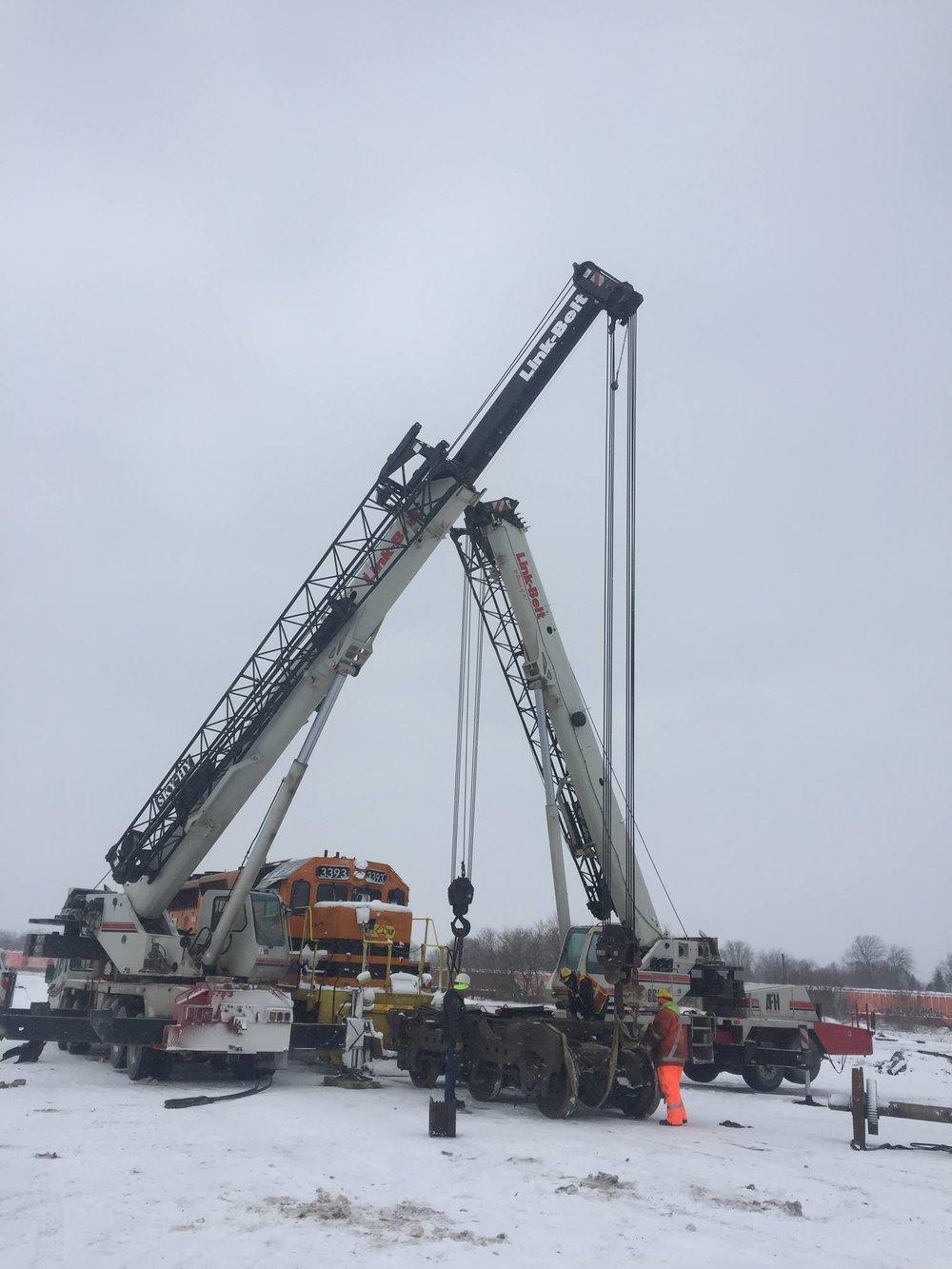2 mobile cranes lift train car to rebuild motor