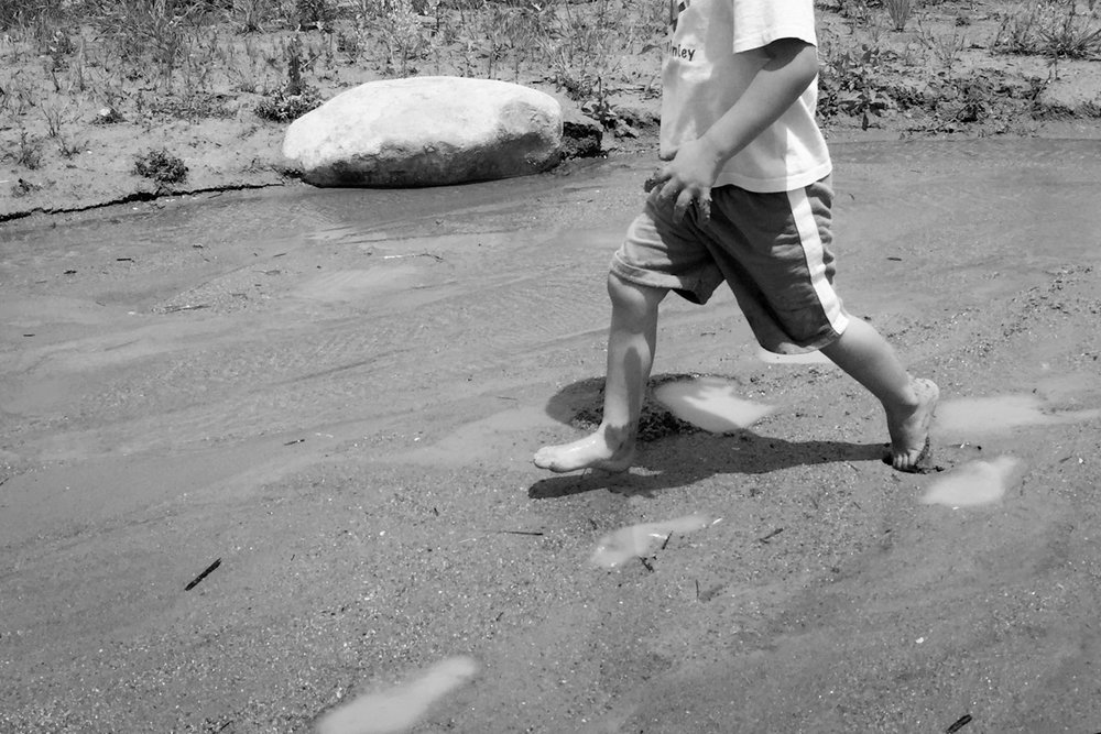 A kid runs in the water stream feature with sand and mud for nature play adventure at  Arapahoe Fairgrounds Park