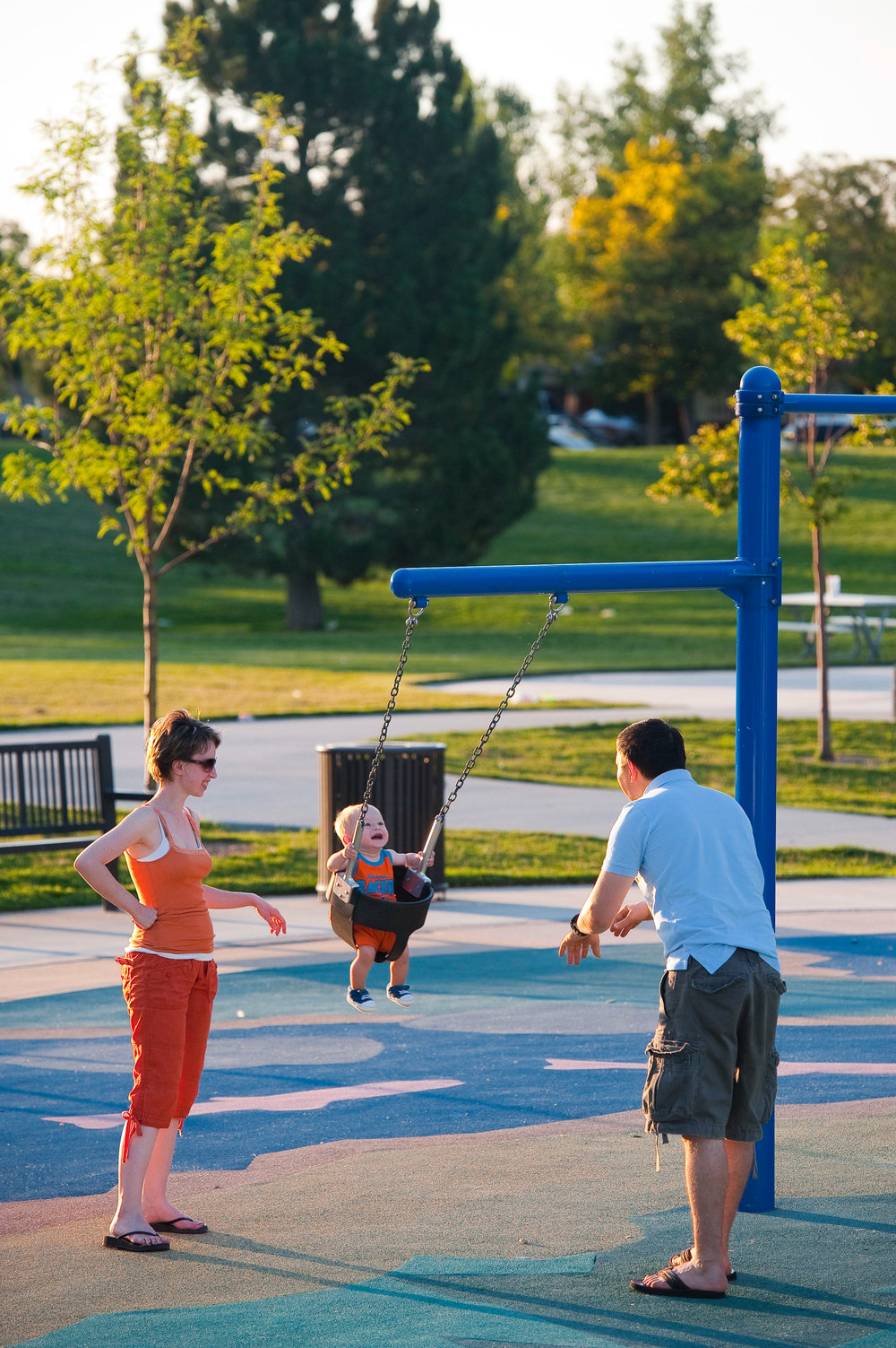 Parents pushing their child on a swing together at a park