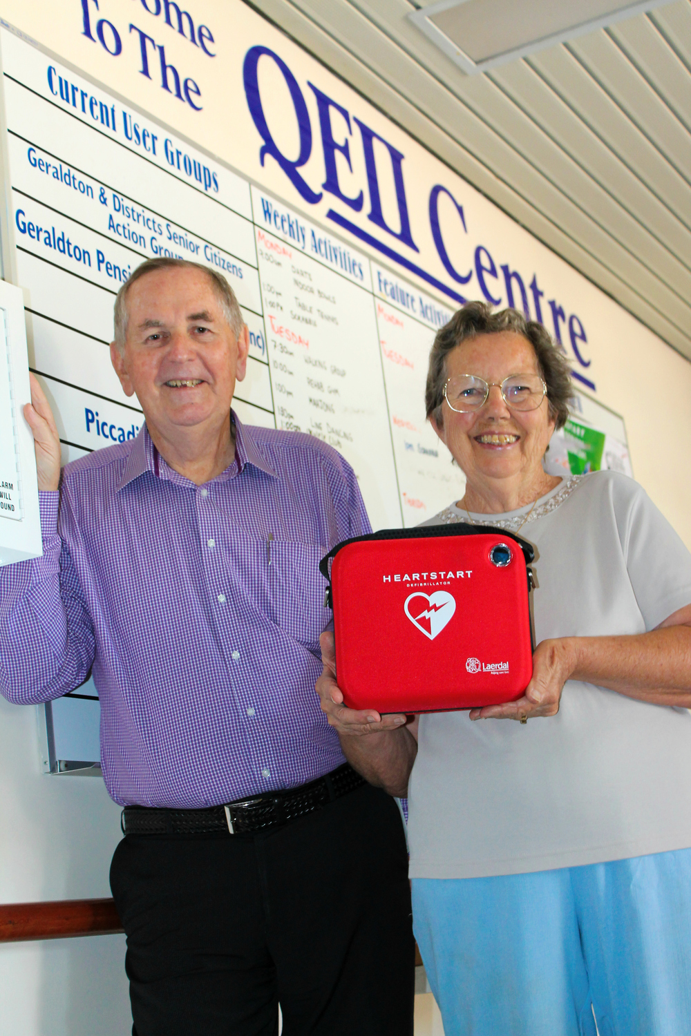 Mayor, Ian Carpenter, and local resident, Irene Shepherd who regularly uses the QEII Centre, showcasing the new defibrillator.