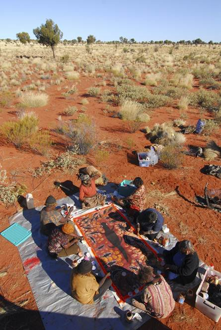 Aboriginal women from Warakurna collaborating on a painting associated with the Lungarta (Blue Tongue lizard) Dreaming. Photo Tim Acker. Courtesy Warakurna Artists
