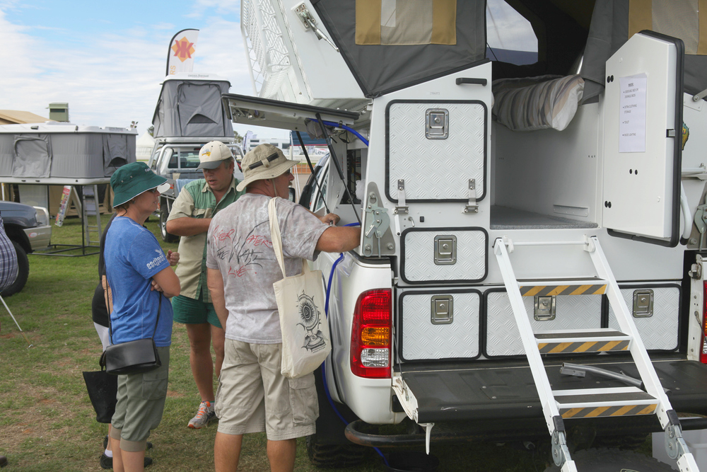 Couple viewing a slide on ute camper at the 2014 Boat, Caravan and Camping Show.