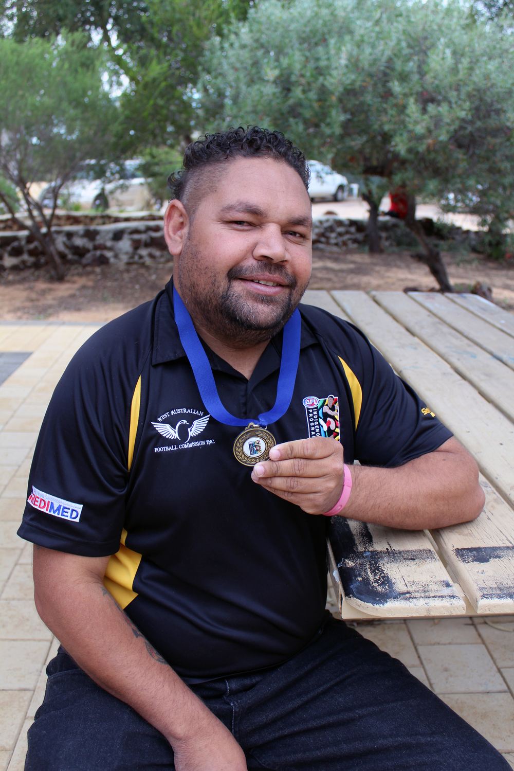 Gordy Clinch with the medal each team member received for winning the National Indigenous KickStart Championship for the fifth consecutive year in Cairns this year.